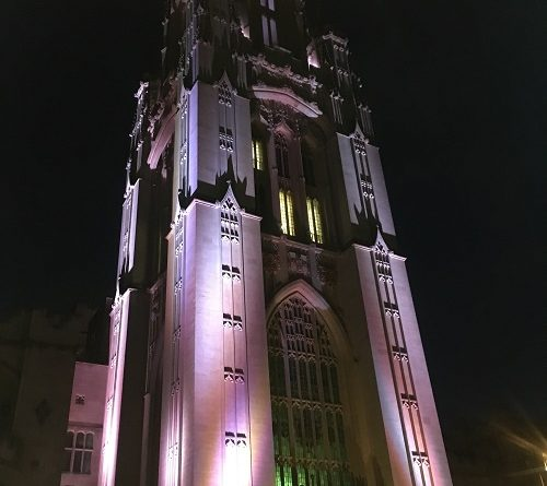 Bristol University Tower Tours. A photo of the Wills Memorial Tower at night lit up in purple lighting