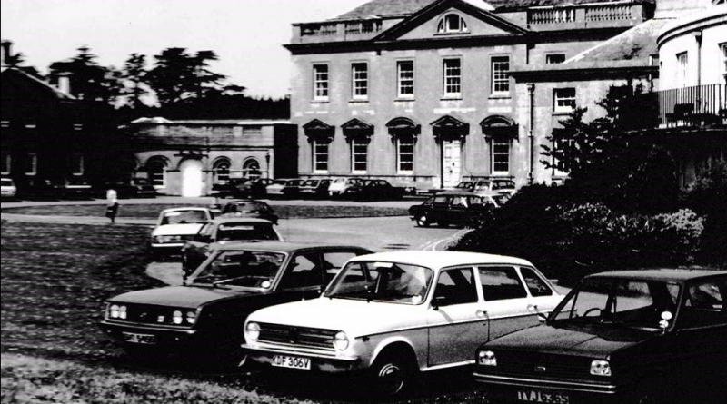 A vintage black and white photo of bath spa university, showing the older mansion house in the background with vintage 1960s cars at the forefront of the image